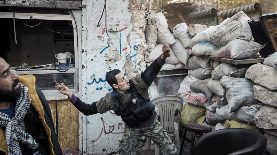To date, Syrian rebels have had to rely on small-scale weapons in their fight against the Syrian army. Here, a rebel fighter throws an explosive device toward a Syrian government position in the northern city of Aleppo last month.