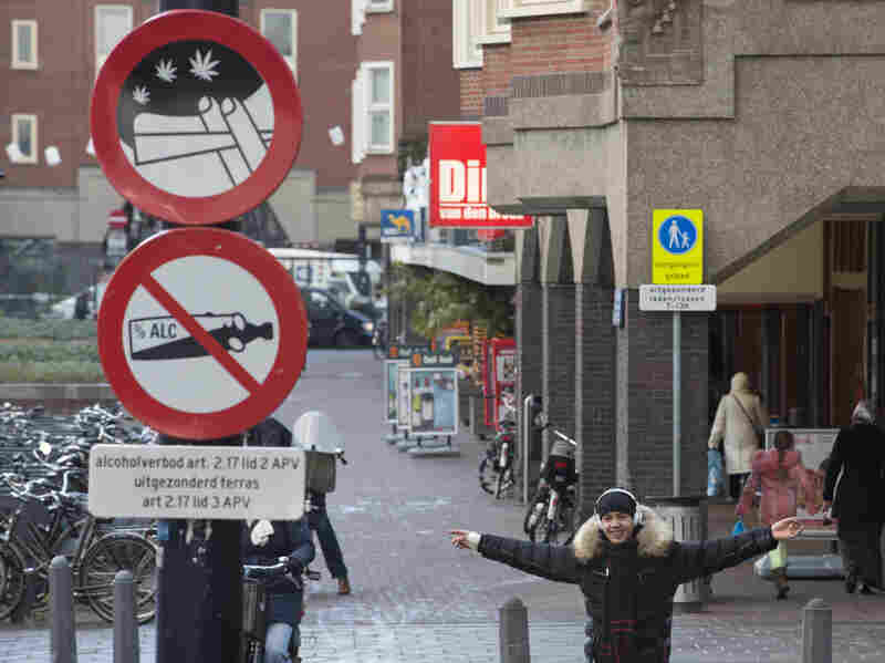 A young man with a joint in his left hand jokes with the photographer as he passes a sign prohibiting the use of marijuana and alcohol, in a designated area in Amsterdam on Wednesday. The city's mayor says students would be formally banned from smoking marijuana at school as of Jan. 1, 2013.