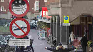 A young man with a joint in his left hand jokes with the photographer as he passes a sign prohibiting the use of marijuana and alcohol, in a designated area in Amsterdam on Wednesday. The city's mayor says students would be formally banned from smoking marijuana at school as of Jan.