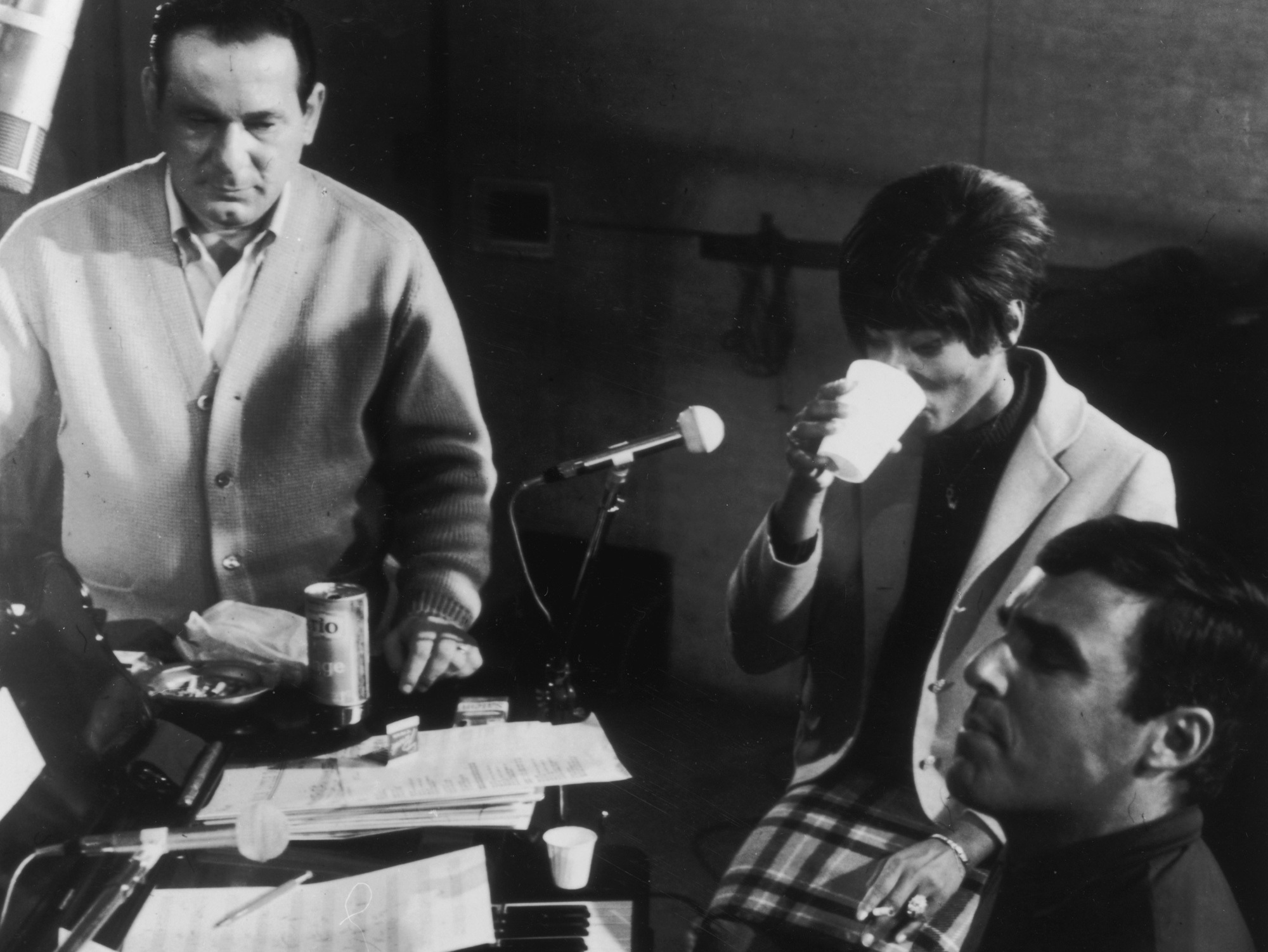 Burt Bacharach plays piano as Dionne Warwick has a drink and American lyricist Hal David looks on, in a 1962 recording session.