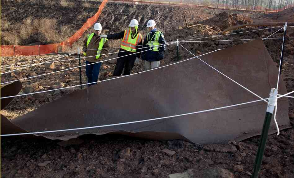 Investigators examine a 20-foot long section of gas pipeline found more than 40 feet from the rupture site north of Charleston, W. Va.