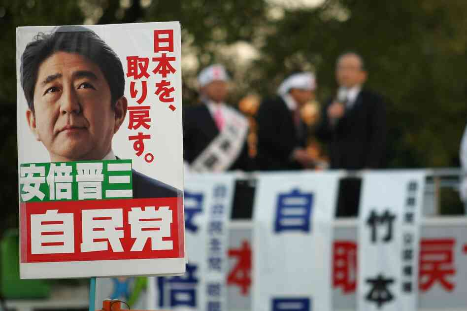 Supporters hold up posters of Japan's former Prime Minister Shinzo Abe at a rally in Osaka on Thursday. Considered a nationalist hawk, Abe is expected to become prime minister for a second time afte