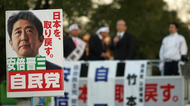 Supporters hold up posters of Japan's former Prime Minister Shinzo Abe at a rally in Osaka on Thursday. Considered a nationalist hawk, Abe is expected to become prime minister for a second time after parliamentary elections Sunday. (Getty Images)
