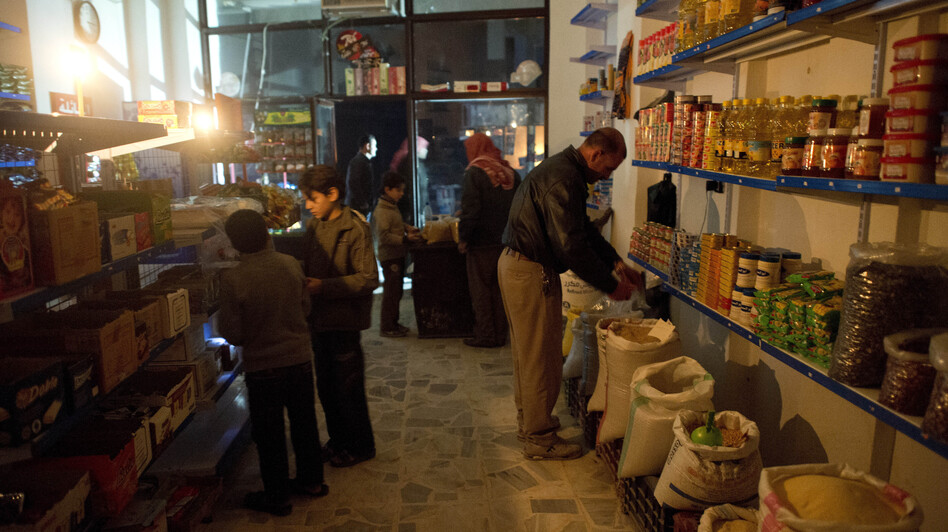 Customers shop by candlelight in a grocery store in Aleppo. The city has been hit hard by fighting in recent months, with both the opposition and the government controlling parts of the area. (AFP/Getty Images)