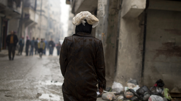 A Syrian woman carries a ration of bread on her head in the northern city of Aleppo. The Syrian opposition now runs local councils in many cities, particularly in the north. They often face major challenges in providing basics likes food, water and electricity. (AFP/Getty Images)