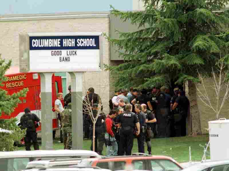 Police gather at the east entrance of Columbine High School in Littleton, Colo., on April 20, 1999. School security has improved markedly since the Columbine shooting, experts say, but there still are problems.