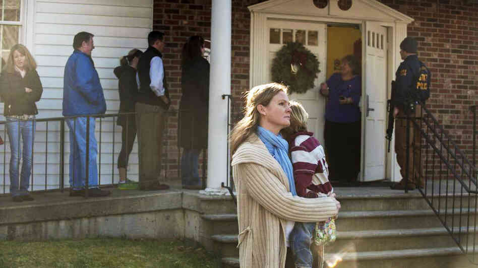 A woman holds a child as people line up to enter the Newtown Methodist Church near the scene of the elementary school shootings in Newtown, Conn.