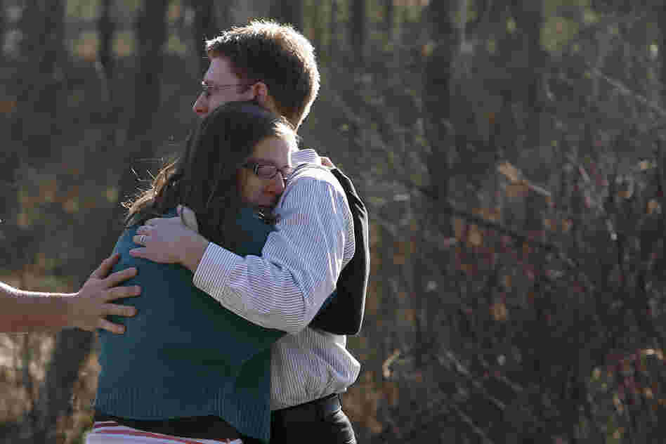 Family members embrace each other near the school.