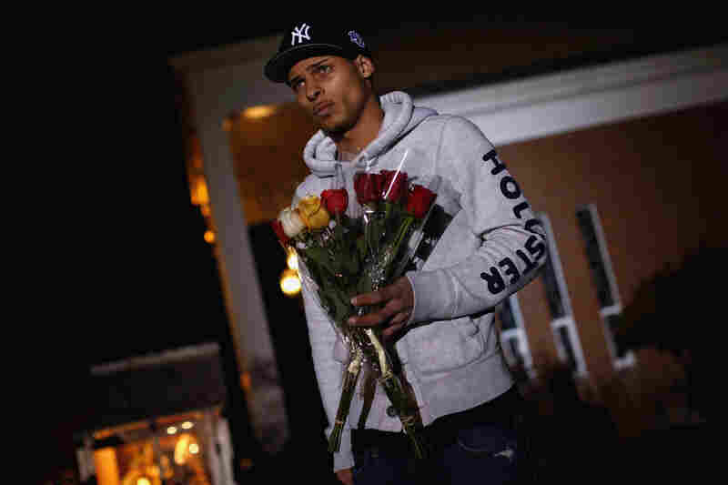 Anthony Baracey holds flowers honoring victims of the Sandy Hook Elementary school killing before a vigil at the Saint Rose of Lima church in Newtown.