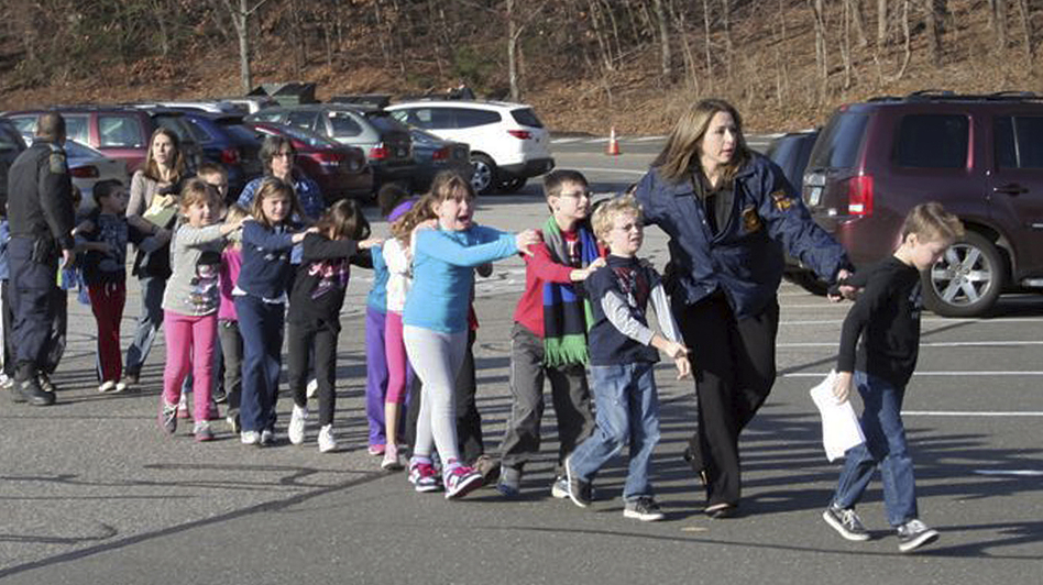 In this photo provided by the Newtown Bee, Connecticut State Police lead children from the Sandy Hook Elementary School in Newtown, Conn., following a shooting there Friday. (Newtown Bee/AP)
