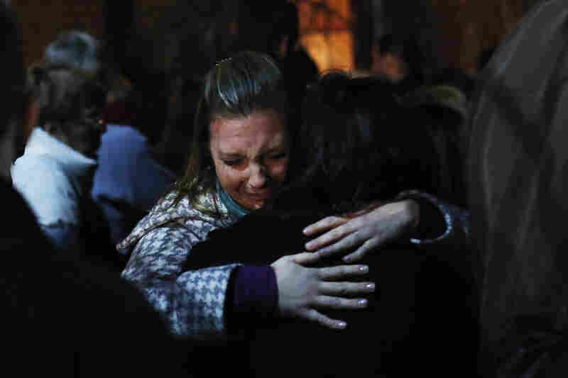 People grieve outside the overflow area of a vigil at the Saint Rose of Lima church in Newtown, Conn., on Friday. A gunman opened fire on schoolchildren and staff in Newtown at Sandy Hook Elementary School today.