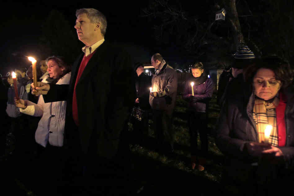 Men and women hold candles in vigil outside St. Rose of Lima Roman Catholic Church during a healing service held in for victims of the shooting at Sandy Hook Elementary School in Newtown, Conn., on Friday.