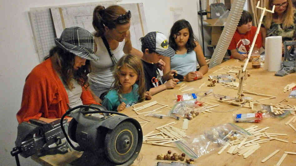 Kids build robots with Popsicle sticks at an Oakland meeting of Hacker Scouts, a group that