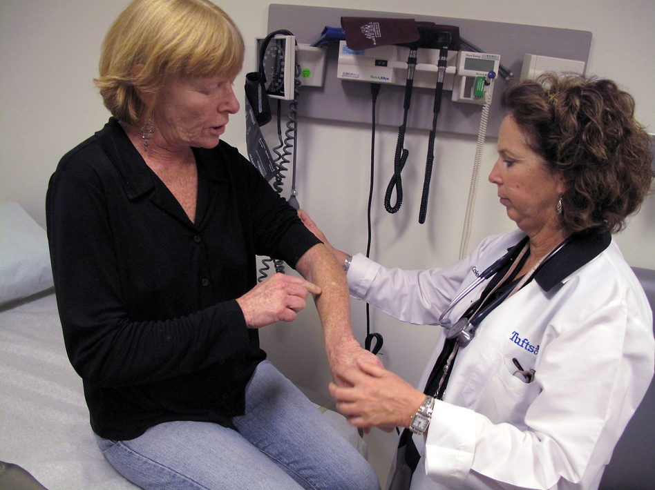 Hepatitis C patient Nancy Turner shows Kathleen Coleman, a nurse practitioner, where a forearm rash, a side effect of her treatment, has healed. Turner is one of many patients with hepatitis C experimenting with new drugs to beat back the virus.