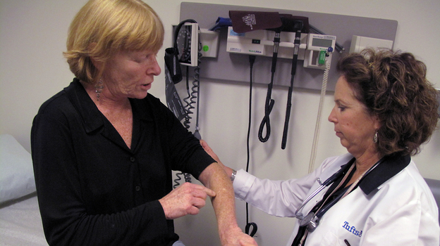Hepatitis C patient Nancy Turner shows Kathleen Coleman, a nurse practitioner, where a forearm rash, a side effect of her treatment, has healed. Turner is one of many patients with hepatitis C experimenting with new drugs to beat back the virus. (NPR)