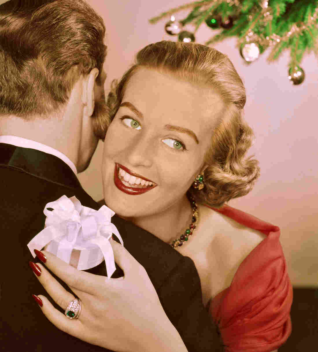 A lady hugs a man whilst she holds onto a Christmas gift wrapped in a bow on December 25, 1955.