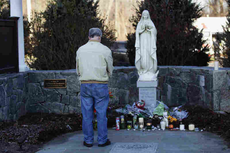 A man stands at a makeshift memorial outside Saint Rose of Lima Roman Catholic Church in Newtown, Conn., on Saturday.