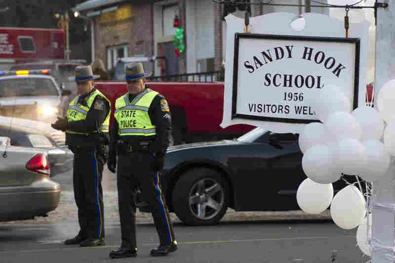 Police stand guard at the entrance to Sandy Hook Elementary School on Saturday in Newtown, Conn.