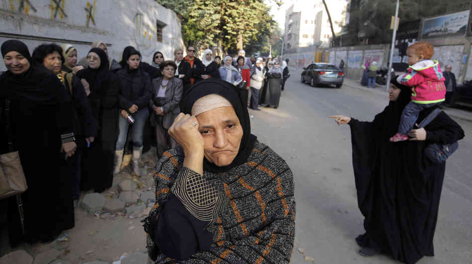 Women wait in line outside a polling station to vote on a disputed const
