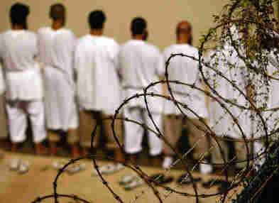 """Detainees stand during an early morning Islamic prayer at the U.S. military prison for """"enemy combatants"""" in Guantanamo Bay, Cuba."""