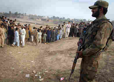 A Pakistani soldier stands guard near a bomb blast site in the outskirts of Peshawar on Dec. 3.
