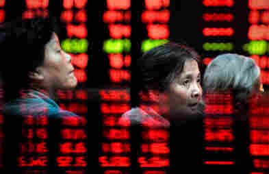 Chinese investors monitor screens showing stock indexes at a trading house in Shanghai.