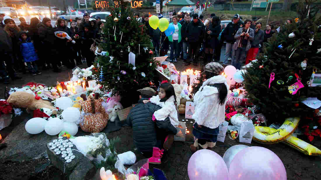 People gather at a memorial for victims near Sandy Hook Elementary School in Newtown, Conn., Sunday. President Obama is visiting the town today to meet with parents and families who lost loved ones in the attack.