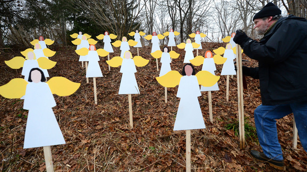 On a hillside in Newtown, Conn., art teacher Eric Mueller sets up wooden angels in memory of the victims of the Sandy Hook Elementary School shooting. Details about the lives of the slain are showing the depths of the community's loss. (AFP/Getty Images)
