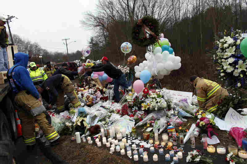 Firefighters and other volunteers organize a memorial near Sandy Hook Elementary School.