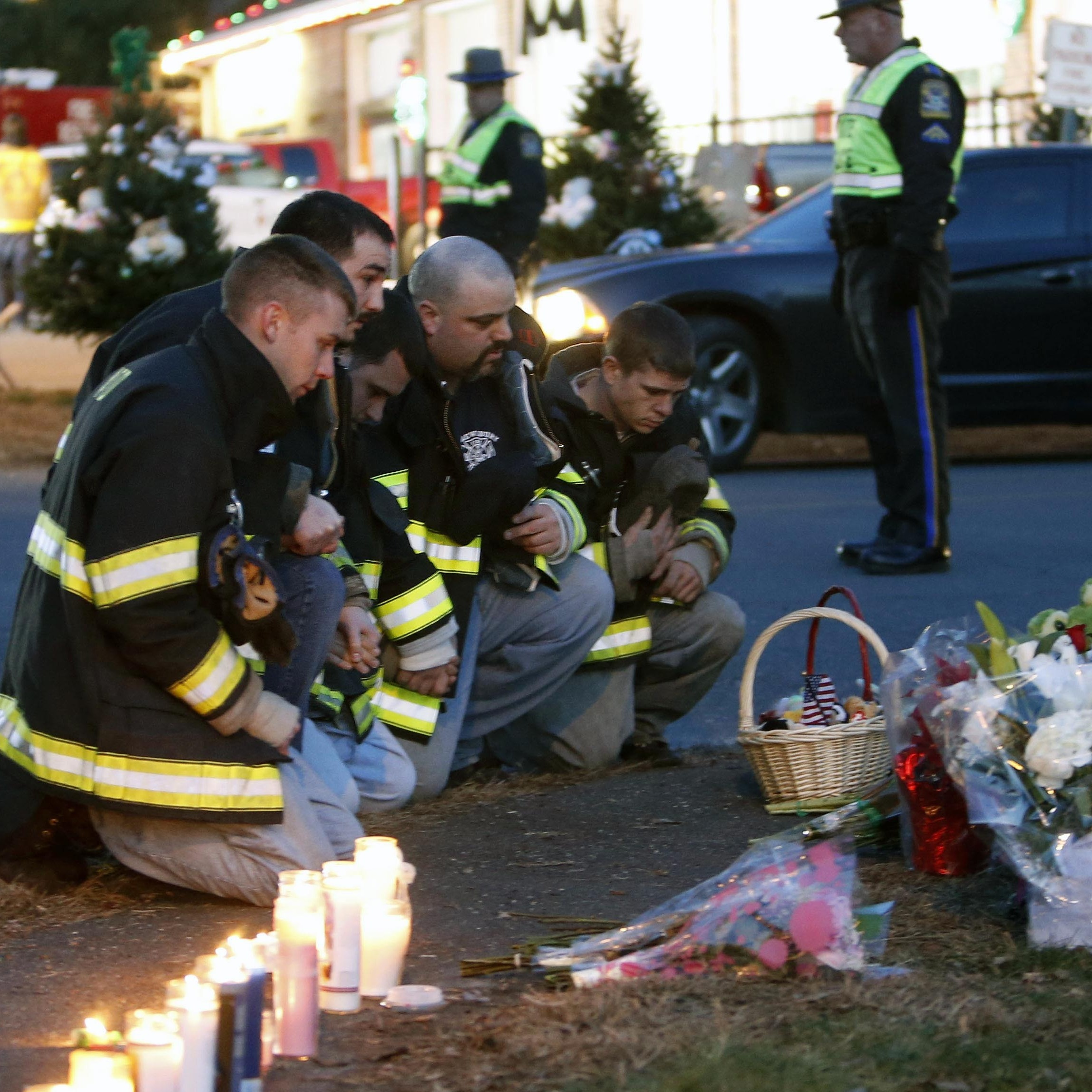 Firefighters pay their respects at a memorial for shooting victims near Sandy Hook Elementary School on Saturday.
