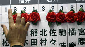 Japan's major opposition Liberal Democratic Party (LDP) Secretary-General Shigeru Ishiba adds a rosette on the name of one of those elected in parliamentary elections at the party headquarters in Tokyo on Sunday.