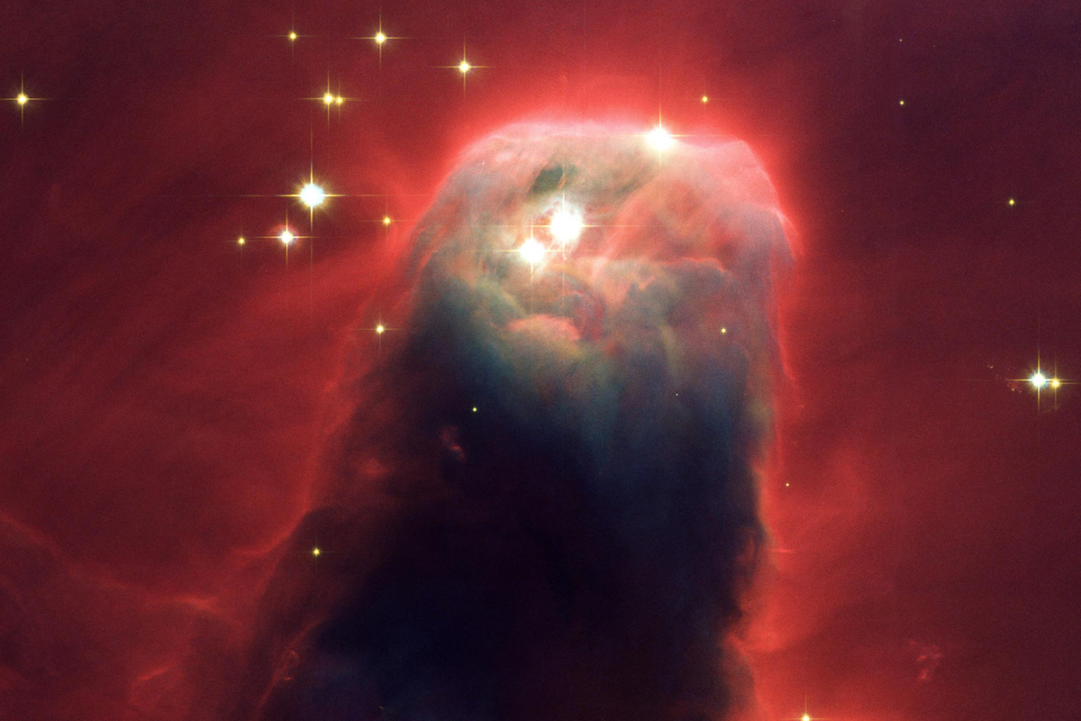 """""""A pillar of gas and dust called the Cone Nebula resides in a turbulent star-forming region."""""""