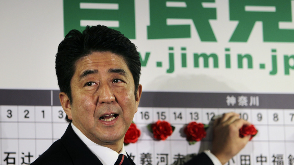 Shinzo Abe of Japan's Liberal Democratic Party marks the name of a parliamentary election winner at party headquarters in Tokyo on Sunday. Japan's conservative LDP stormed back to power Sunday after three years in opposition. (AP)