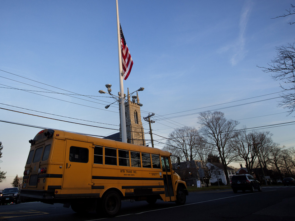 Friday afternoon: As a bus took some students home in Newtown, Conn., the flag was already at half-staff to honor the first-graders and school staff killed that morning. (Shannon Stapleton /Reuters /Landov)