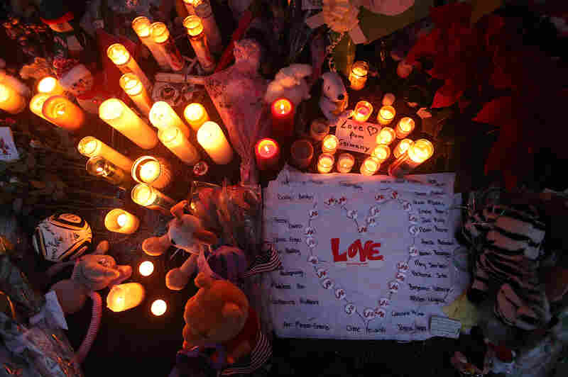 Candles are lit among mementos at a memorial for victims of the shooting on Monday night in Newtown.