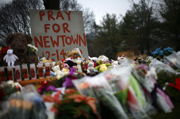 Flowers, candles and stuffed animals make up a makeshift memorial in Newtown, Conn., on Monday. Much of the initial news coverage of Friday's events was later fou
