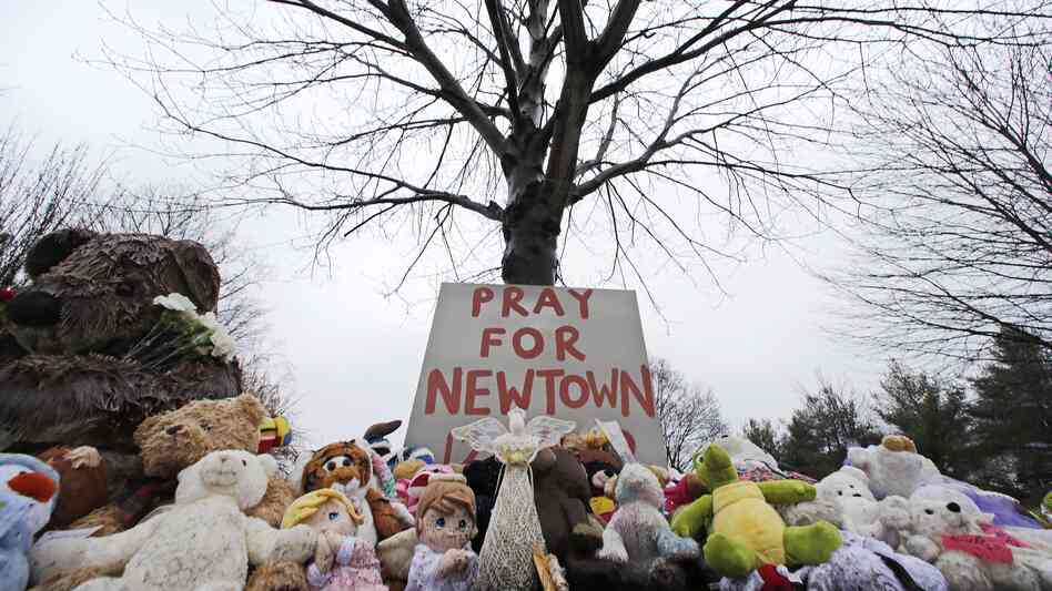 Stuffed animals and a sign calling for prayer lay at the base of a tree near the Newtown Village Cemetery in Newtown, Conn., on Monday, in remembrance of the victims of the mass shooting at Sandy Hook Elementary School.