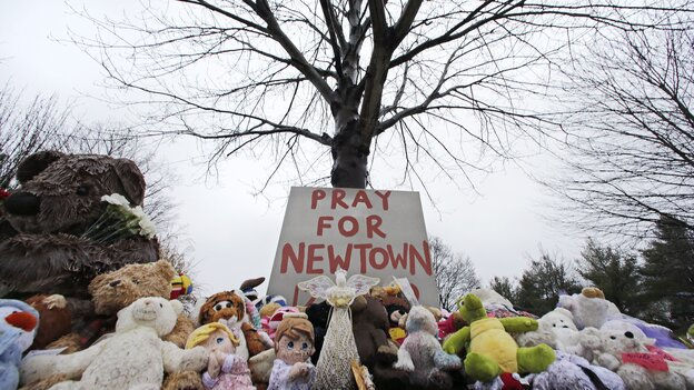Stuffed animals and a sign calling for prayer lay at the base of a tree near the Newtown Village Cemetery in Newtown, Conn., on Monday, in remembrance of the victims of the mass shooting at Sandy Hook Elementary School. (AP)