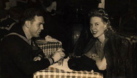 Creore sits with a sailor at the Stage Door Canteen in New York.