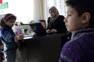 Principal Sally Albunni enrolls  Nureddin, 11, (right) who arrived in Antakya with his mother after his father was killed two weeks earlier in Syria.