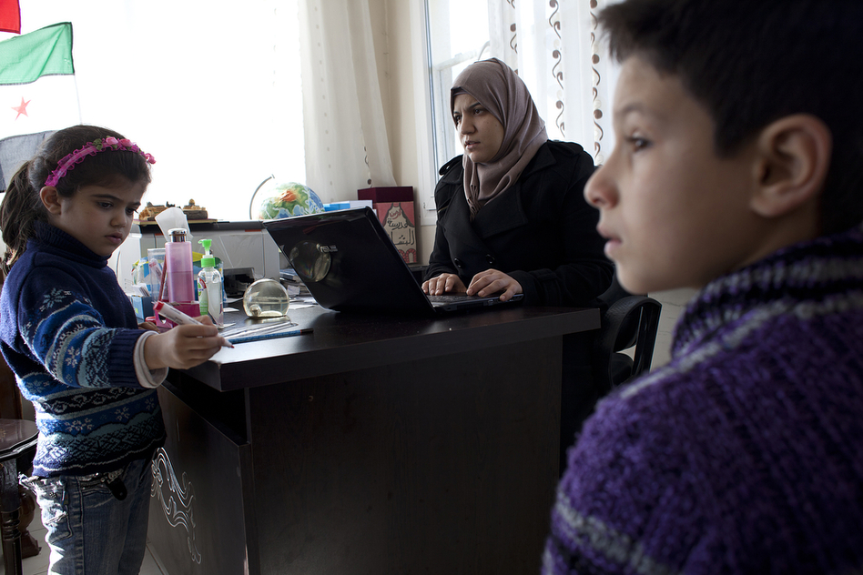 Principal Sally Albunni enrolls  Nureddin, 11, (right) who arrived in Antakya with his mother after his father was killed two weeks earlier in Syria. (Jodi Hilton for NPR)