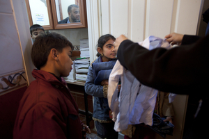 Cousins Suleiman Selmo, 9, and Kawthar Selmo, 10, receive donated clothes on their second day at the school. Many Syrian children and families are in need of basic supplies.