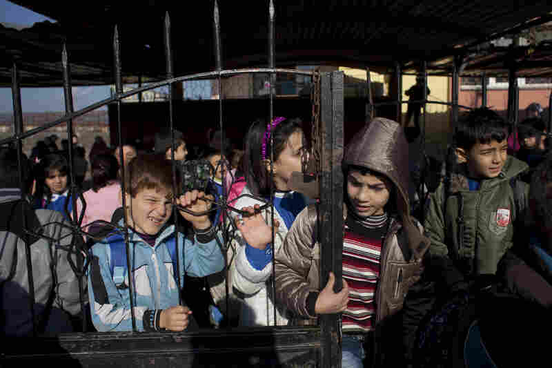 Children wait for minibuses to take them home after school. The school is free for Syrian children living in Turkey.