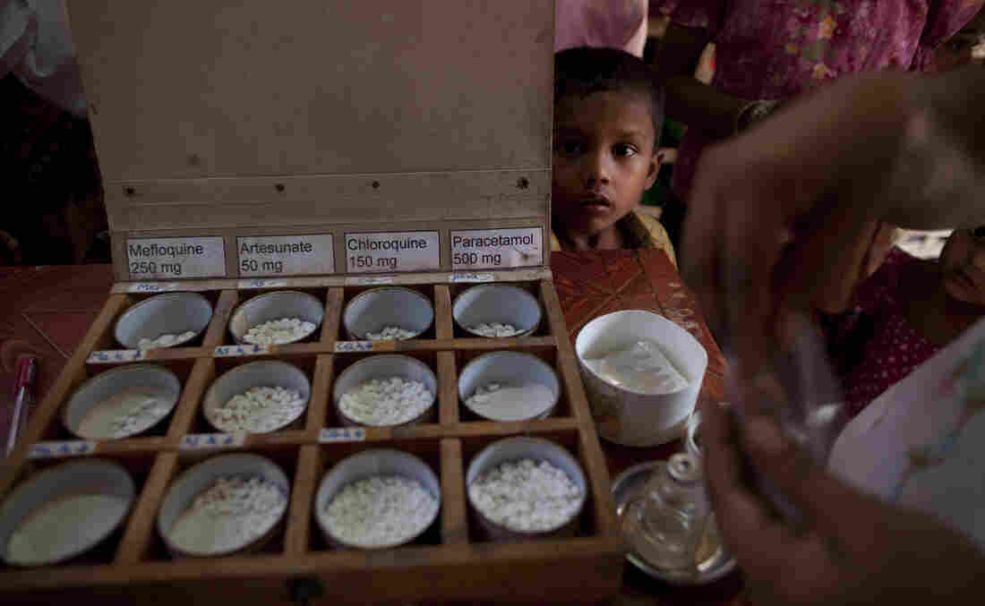 A boy watches as malaria medicine is given out to patients at a malaria clinic in Sittwe, Myanmar. Shoddy and phony malaria drugs are a longstanding problem in the country.