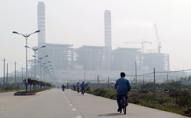 China and India are projected to propel coal's challenge of oil as the world's top energy source within the next five years, according to a new study. Here, a man rides a bicycle toward a coal-fired power station in China's Guangdong province last year.