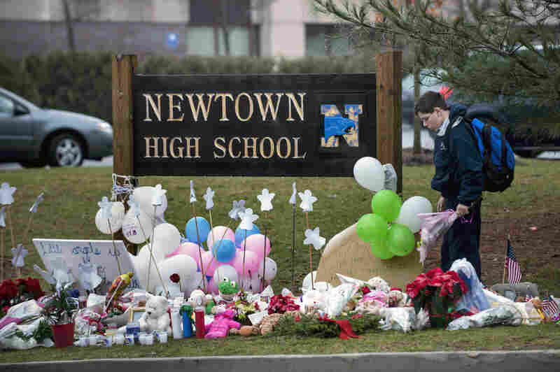 A student looks for a place to leave flowers at a makeshift memorial for the victims of the Sandy Hook Elementary School shooting at the entrance of Newtown High School on Tuesday in Newtown, Conn.