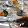 A dining table set for the holidays with linens, candlesticks, clementines and gourds.