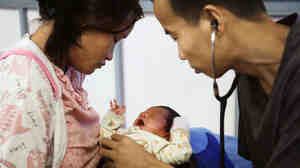 Dr. Aun Pyae Phyo examines a baby at the Whampa malaria clinic on the Thailand-Myanmar border.