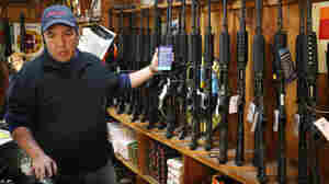 At the Freddie Bear Sports shop in Tinley Park, Ill., Jason Zielinski shows AR-15 style rifles to a customer.