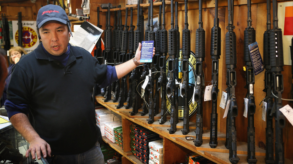 At the Freddie Bear Sports shop in Tinley Park, Ill., Jason Zielinski shows AR-15 style rifles to a customer. (Scott Olson/Getty Images)